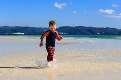 Weinig jongen die op zandstrand lopen Stock Foto's