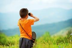 Weinig jongen die openlucht door verrekijkers kijken Hij wordt verloren Royalty-vrije Stock Foto's