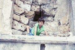 Weinig jongen die oude architectuur, levensstijlmensen op de zomervakantie dicht onderzoeken omhoog stock afbeelding