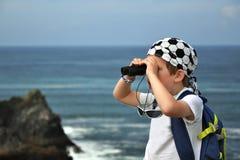 Weinig jongen die overzees landschap met verrekijkers onderzoekt Stock Afbeeldingen