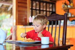 Weinig jongen die pannekoeken in koffie eten Stock Foto