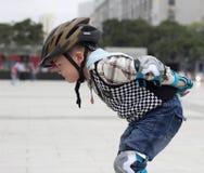Weinig jongen die in park schaatsen Stock Foto's