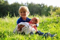 Weinig jongen die pasgeboren zuster in de zomeraard houden Stock Afbeelding