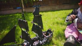 Weinig jongen die piraatkostuum dragen bekijkt schatkaart met kijker Piraatstuk speelgoed schip en fles rum op stock footage