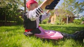 Weinig jongen die piraatkostuum dragen speelt in piraatstuk speelgoed schip op het gazon stock footage