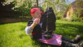 Weinig jongen die piraatkostuum dragen speelt in piraatstuk speelgoed schip op het gazon op Halloween stock footage