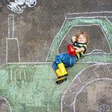 Weinig jongen die pret met de tekening van het tractorbeeld met krijt hebben stock foto