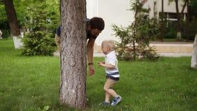 Weinig jongen die pret met zijn vader in een groen park hebben Het spelen zoekt en verbergt Het leuke, grappige kind verbergen ac stock footage