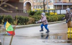 Weinig jongen die in regenachtig de zomerpark spelen Het kind met kleurrijke regenboogparaplu, maakt laag en laarzen springend in Stock Foto
