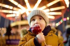 Weinig jongen die rode die appel eten in karamel op Kerstmismarkt wordt behandeld Traditionele child& x27; s plezier en pret tijd royalty-vrije stock foto's