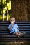 Weinig jongen die roomijs in de dag van de parkzomer eten Royalty-vrije Stock Afbeelding