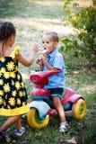 Weinig jongen die roomijs eten zit op kleine driewieler terwijl zijn sist Royalty-vrije Stock Foto