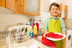 Weinig jongen die schone plaat in de keuken afvegen royalty-vrije stock fotografie