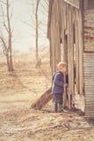 Weinig jongen die in schuur kijken Stock Foto's