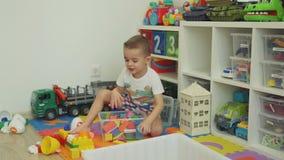 Weinig jongen die speelgoed in zijn ruimte organiseren stock footage