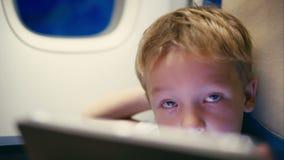 Weinig jongen die tabletcomputer met behulp van tijdens vlucht stock video