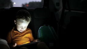 Weinig jongen die tabletpc met behulp van tijdens autoreis bij stock footage