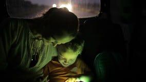 Weinig jongen die tabletpc met behulp van tijdens autoreis bij stock videobeelden