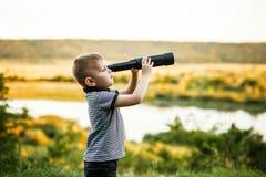 Weinig jongen die telescoopooglens onderzoeken stock foto