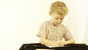 Weinig jongen die thuiswerk doet stock video