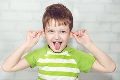 Weinig jongen, die trekken op de oren Stock Foto's