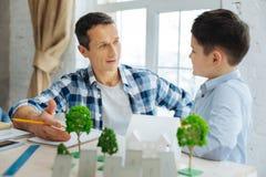 Weinig jongen die vader vragen over zijn werk als architect royalty-vrije stock afbeeldingen