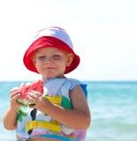 Weinig jongen die van één of andere watermeloen geniet Stock Afbeelding