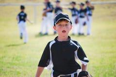 Weinig jongen die van het ligahonkbal op gebied lopen Stock Foto