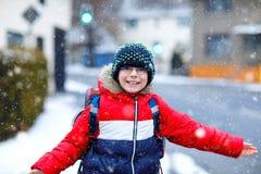 Weinig jongen die van het schooljonge geitje van elementaire klasse aan school tijdens sneeuwval lopen Gelukkig kind die pret heb stock foto