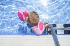 Weinig jongen die van veiligheid genieten bij zwembad stock fotografie