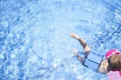 Weinig jongen die van veiligheid genieten bij zwembad royalty-vrije stock afbeeldingen