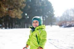 Weinig jongen die van zijn tijd in de sneeuw genieten stock afbeelding