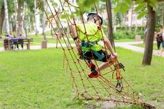 Weinig jongen die in veiligheidsmateriaal op kabelmuur bij avonturenpark beklimmen De sport extreme openluchtactiviteit van de ki stock afbeelding