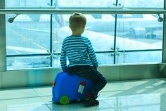 Weinig jongen die vliegtuigen in de luchthaven bekijken Stock Fotografie