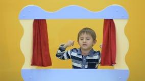 Weinig jongen die voor het scherm van poppenspel voor de gek houden stock footage