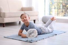 Weinig jongen die voor ventilator thuis ontspannen stock foto's