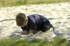 weinig jongen die in zand speelt Stock Afbeelding