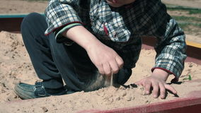 Weinig jongen die in zandbak langzaam-mo spelen stock video