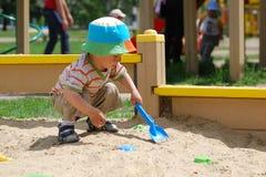 Weinig jongen die in zandbak speelt Stock Foto's