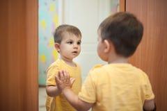 Weinig jongen die zich dichtbij spiegel bekijken; royalty-vrije stock afbeeldingen