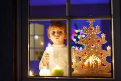Weinig jongen die zich door venster in Kerstmistijd bevinden Stock Foto