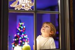Weinig jongen die zich door venster in Kerstmistijd bevinden Stock Foto's