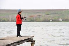 Weinig jongen die zich op de pier met een spinnende staaf bevinden. Stock Foto