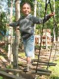 Weinig jongen die zich op een houten ladder bevinden en de kabel houden stock afbeelding