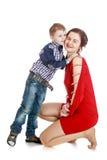 Weinig jongen die zijn geliefde moeder kussen Stock Foto's