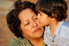 Weinig jongen die zijn grootmoeder kust Stock Foto