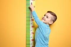 Weinig jongen die zijn hoogte meten stock fotografie