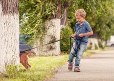 Weinig jongen die zijn puppy lopen Stock Fotografie