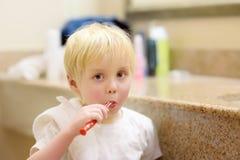 Weinig jongen die zijn tanden borstelt stock fotografie