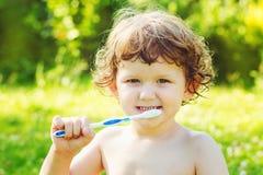 Weinig jongen die zijn tanden op groene achtergrond borstelen stock afbeeldingen